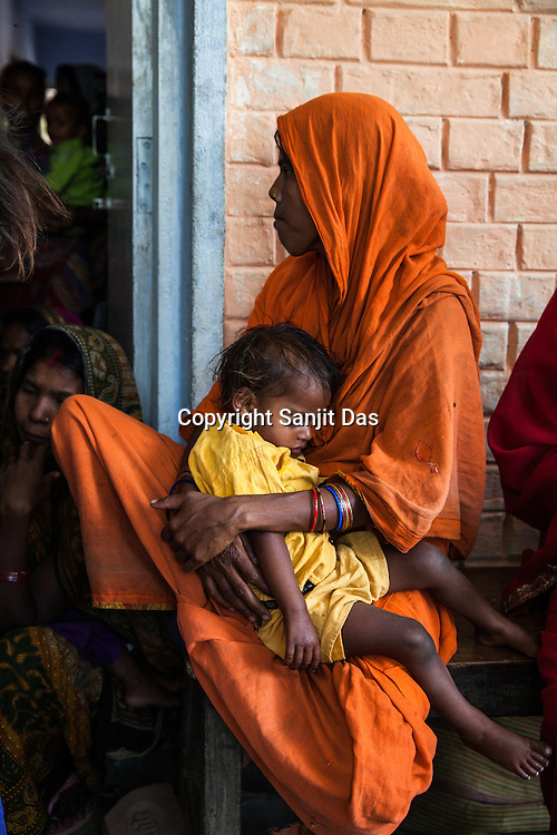 25 year old Dayawati and her 17 month son, Naresh Mukhiya wait to meet the Health workers at the local health centre in Hanuman Nagar in Saptari, Nepal. <br /> Naresh Mukhiya was first admitted on July 17, 2013 when he was 9 months old. MUAC - 109 mm, Weight - 5.5kg, and Height - 65 cm. He was discharged on Oct 1st, 2013. MUAC at the time of discharge - 123, Weight - 6.5 Kg, Height - 66cm. Total RUTF consumes - 148 sachets.Gain of weight - 2gm.day.