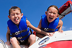 USA, Missouri, Stockton, Stockton Lake, boy (6-7) and girl (8-9) on boat making faces