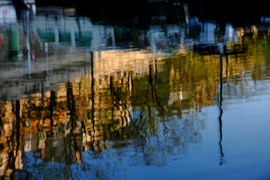 A reflected image of boats at the sunrise in the water of the basin of the port de l'Arsenal, in Paris. Digitally Improved Photo.