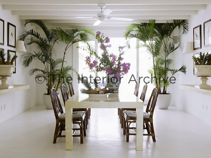 A set of rattan chairs surround a leather-upholstered table in this all white dining room