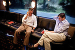 GOP presidential candidate Gov. Mitt Romney takes a call with strategist Russ Schriefer, right, on his ccampaign bus after  a campaign rally at Carter Machinery Company in Salem, Virginia, June 26, 2012.