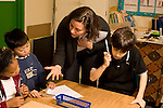 Education elementary Grade 3 science classroom female teacher explaining experiment method to male and female students male student nearby using tuning fork horizontal