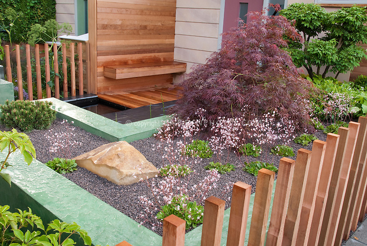Beautifully landscaped entry of house with Japanese maple tree, Saxifraga in flowers, fence, stones, boulders, wood and upscale touches creating a sense on an outdoor room enclosed by open posts