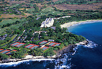 Aerial shot of the Mauna Kea Beach Hotel on the Big Island, with tennis courts, golf course and lush grounds next to white sand beaches and the beautiful blue Pacific Ocean.