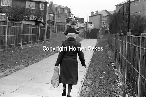 Wandsworth south London 1970s Black African woman returns home from the Arndale shopping Centre.