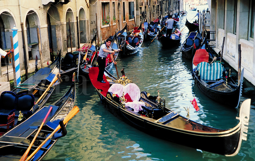 A gondolier navigates his craft through the crowded canals of Venice, Italy. boat, boats, transportation, cityscape, waterways, urban structure, occupations. Venice, Italy.