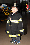 firefighter fire child boy male childhood dreams ems emergency safety communication engine person 911 confidence courage brave crisis dedication call male man teamwork dependence masculinity pride job career occupation department rescue risk news service security strength uniform gear copy space equipment portrait firefighting