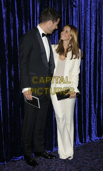 Jamie Redknapp & Louise Redknapp.attended the Retail Trust London Ball, Grosvenor House Hotel, Park Lane, London, England..January 28th, 2013.full length white blazer top trousers suit black clutch bag tuxedo married husband wife looking up down profile .CAP/CAN.©Can Nguyen/Capital Pictures.