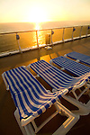 Cruiseship deck with deck chairs at sunset