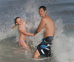 Father and daughter face a splashing waves at Sandys Beach, Hawaii.