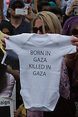 "London, UK. 26 July 2014. A woman holds up a baby romper with the slogan ""Born in Gaza, killed in Gaza"". Protesters gather in Parliament Square and Whitehall after a march from the Israeli Embassy in Kensington to call for an end to the Israeli military action against the Palestinians in the Gaza Strip at a political rallye."