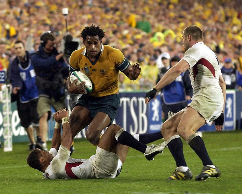 Photo: Richard Lane..Australia v England. Rugby World Cup Final, at the Telstra Stadium, Sydney. RWC 2003. 22/11/2003. .Lote Tuqiri is tackled by Jason Robinson.