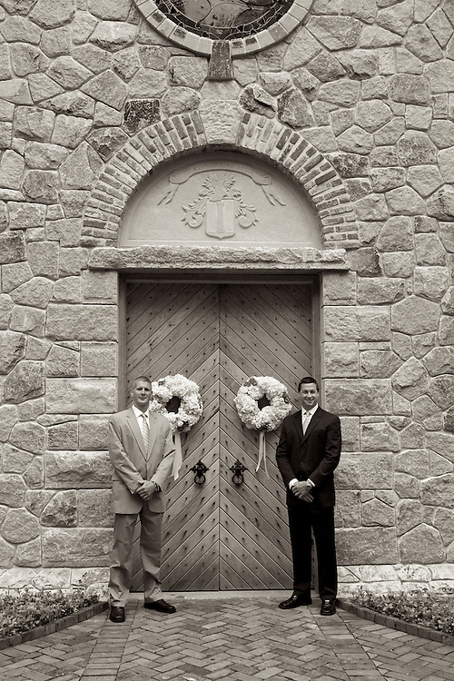 Black & white sepia photo of ushers standing outside the doors of the chapel ready to receive guests.