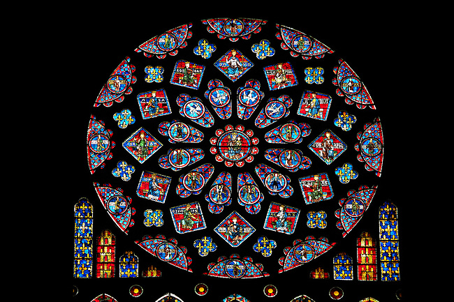 Medieval Rose Window of the North Transept of the Gothic Cathedral of Chartres, France- Circa 1235. A UNESCO World Heritage Site. The 10.5m rose window is dedicated to the Virgin Mary . The central oculus shows the Virgin and Child and is surrounded by 12 small petal-shaped windows, 4 with doves (the 'Four Gifts of the Spirit'), the rest with adoring angels carrying candlesticks. Beyond this is a ring of 12 diamond-shaped openings containing the Old Testament Kings of Judah, another ring of smaller lozenges containing the arms of France and Castille, and finally a ring of semicircles containing Old Testament Prophets holding scrolls. The presence of the arms of the French king (yellow fleurs-de-lis on a blue background) and of his mother, Blanche of Castile (yellow castles on a red background) are taken as a sign of royal patronage for this window. Beneath the rose itself are five tall lancet windows (7.5m high) showing, in the centre, the Virgin as an infant held by her mother, St Anne - the same subject as the trumeau in the portal beneath it. Flanking this lancet are four more containing Old Testament figures. Each of these standing figures is shown symbolically triumphing over an enemy depicted in the base of the lancet beneath them - David over Saul, Aaron over Pharaoh, St Anne over Synagoga, etc