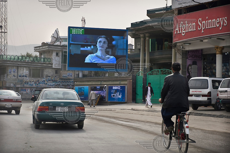 A huge electronic billboard plays advertisements, among them videos featuring women in Western style clothing.