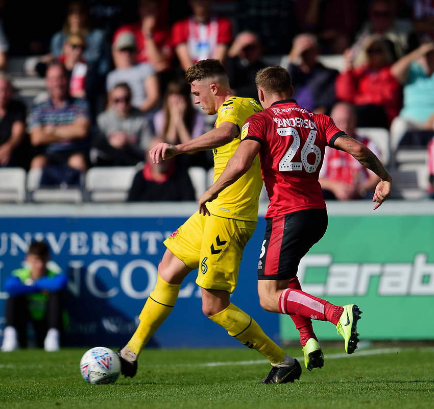 Fleetwood Town's Harry Souttar clears under pressure from Lincoln City's Harry Anderson<br /> <br /> Photographer Andrew Vaughan/CameraSport<br /> <br /> The EFL Sky Bet League One - Lincoln City v Fleetwood Town - Saturday 31st August 2019 - Sincil Bank - Lincoln<br /> <br /> World Copyright © 2019 CameraSport. All rights reserved. 43 Linden Ave. Countesthorpe. Leicester. England. LE8 5PG - Tel: +44 (0) 116 277 4147 - admin@camerasport.com - www.camerasport.com