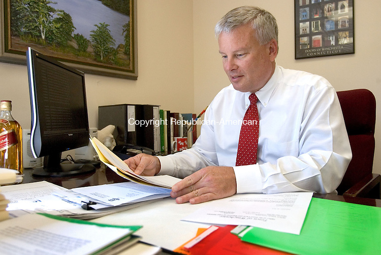WINSTED CT. 19 September 2014-091914SV04-Dale L. Martin, town manager, works at his desk in Town Hall in Winsted Friday. Martin returned to work after the selectmen voted to reinstate him. The selectmen voted a month ago along party lines to suspend him with the intention of firing him a month later. The Republican selectmen had lost confidence in him. <br /> Steven Valenti Republican-American