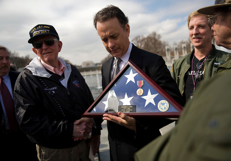 "Actor and producer Tom Hanks, poses for a picture with a World War II veteran and the flag of a deceased veteran, after a tribute to honor WW II vets that served in the Pacific Theater, March 11, 2010.  The event was held at the World War II Memorial on the Mall and coincides with the upcoming HBO miniseries entitled ""The Pacific."""