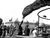 A fairgoer offers his hat toa dinosaur at the Sinclair Oil display at the 1933 Chicago World's Fair.(Photographer Unknown/www.bcpix.com)