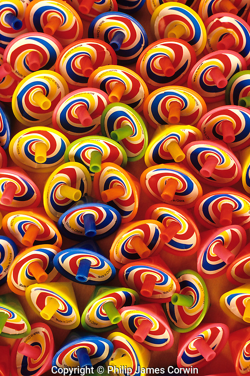 Multi-colored spinning tops all in rows making a background pattern.