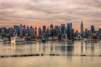 The rising sun shines through the buildings of the Manhattan skyline and reflects off the clouds a few minutes after sunrise as viewed over the Hudson River looking east from New Jersey.