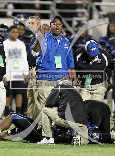 First Coast Buccaneers assistant coach questions a call as an injured player is looked at during the Florida High School Athletic Association 7A Championship Game at Florida's Citrus Bowl on December 16, 2011 in Orlando, Florida.  Manatee defeated First Coast 40-0.  (Photo By Mike Janes Photography)