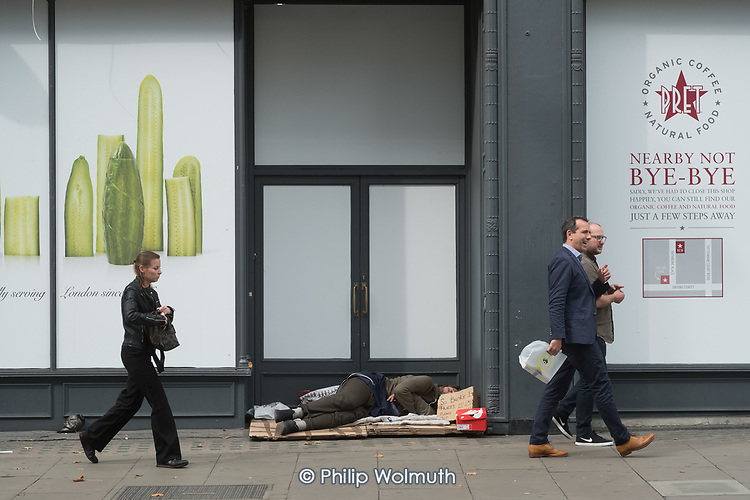 Homeless man sleeping in dooreway of closed Pret a Manger store, Oxford Street, London.
