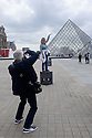 Paris, France. 09.05.2015. Tourist posing for a photo in front of the Louvre pyramid. Photograph © Jane Hobson.