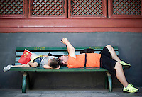 A Chinese man takes a selfie on a bench close to his son at the Yonghe Temple (Chinese 雍和宮, pinyin Yōng hé gōng), also known as the Lama Temple in Beijing, China, August 15, 2014.<br /> <br /> Smartphones are an essential tool of Chinese ordinary life. Everywhere in China, people use them to take pictures to share online, to talk and chat, to play videogames, to get access to the mainstream information, to get connected one each other. In the country where the main global social media are forbidden - Facebook, Twitter and Youtube are not available  -, local social networks such as WeChat have a wide spread all over the citizens. The effect is an ordinary and apparently compulsive way to get easy access to digital technology and modern way of communication. <br /> A life through the display. Yes, We Chat.<br /> <br /> © Giorgio Perottino