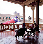 A couple enjoys cocktails on the upstairs balcony of the historic Driskill Hotel in Austin, TX