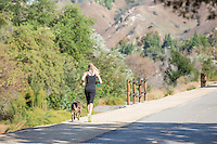 Girl Running with her Dog on Trail