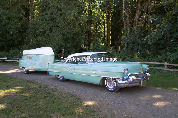 1956 turquoise Cadillac Sedan De Ville (4 door) with a white top. Behind the Cadillac is a turquoise and white 1956 Kom-Pak Sportsman vintage travel trailer/trailerboat.