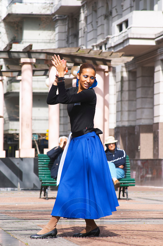 Plaza de Cagancha Square, a couple man and woman dancing flamenco and tango on a city square, dressed in blue skirt black top, white pants, blue shirt and black hat. Woman clapping hands and two onlookers watching. Montevideo, Uruguay, South America