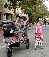2 1/2-year-old Maeze Mooney pushes her baby in her baby stroller as her mom Kelly pushes her double stroller with her brother Jameson down Main Street during the last First Friday of the year in Old Town Warrenton.