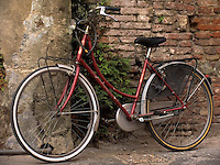Red bicycle leaning agains brick wall, Lucca, Ital