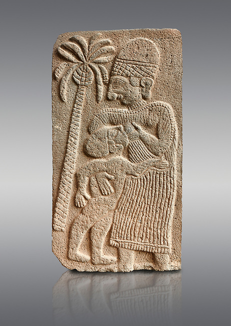 Pictures & images of the North Gate Hittite sculpture stele depicting a women breast feeding a child. 8the century BC.  Karatepe Aslantas Open-Air Museum (Karatepe-Aslantaş Açık Hava Müzesi), Osmaniye Province, Turkey. Against grey background