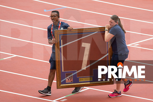 Staff carry of a framed piece of the 2012 track presented to Mo Farah moments before during the IAAF Diamond League Muller London Anniversary Games 2017 at the Queen Elizabeth Park, Olympic Park, London, England on 9 July 2017.  Photo by Andy Rowland.