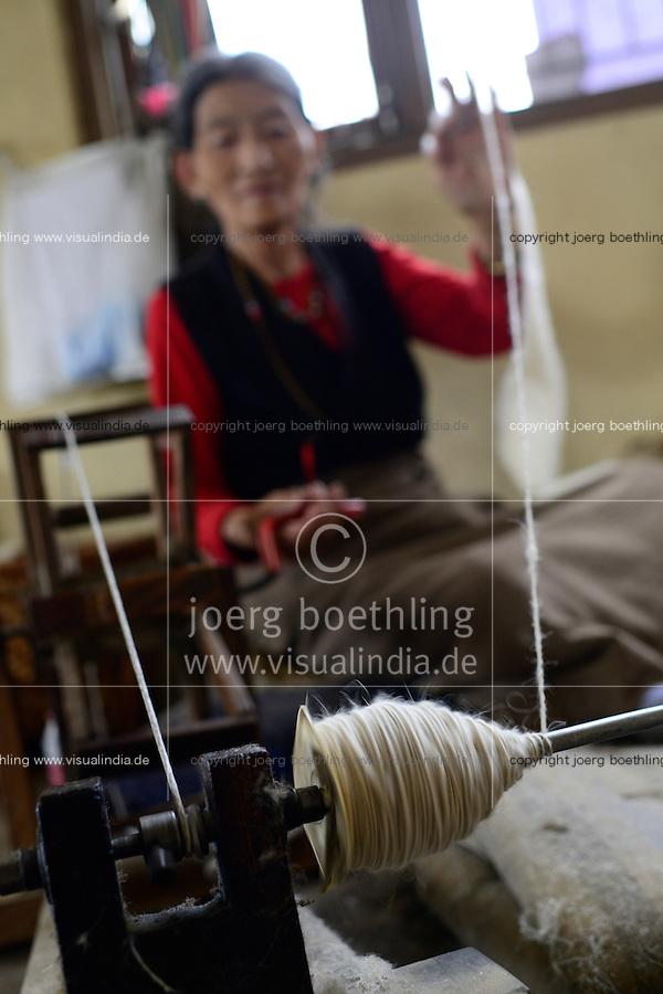 NEPAL Kathmandu, Lalitpur, tibetan refugee camp Jawalakhel, carpet factory JHC Jawalakhel Handicraft Center, tibetan women spin wool for carpets for income generation /  tibetische Fluechtlinge, tibetisches Fluechtlingslager Jawalakhel, Teppichfabrik JHC Jawalakhel Handicraft Center, tibetische Frauen spinnen die Wolle