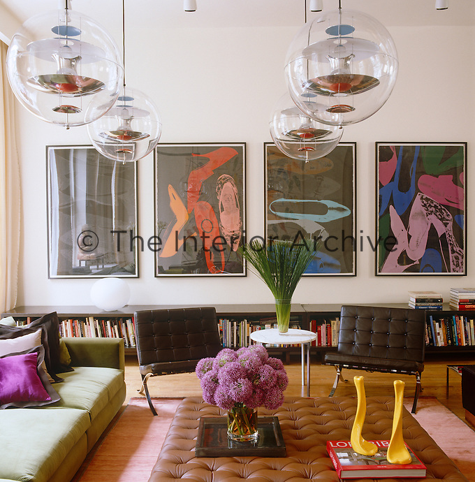 "Four Verner Panton Globe lights hang above the living area and on the wall behind is a group of silk-screen prints by Andy Warhol from the ""Diamond Dust"" series"