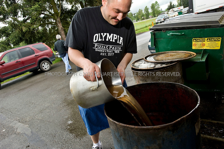 5/20/2008--Arlington, WA, USA..Nick Damianidis, whose family owns Olympia Pizza and Pasta in Arlington, Wash., pours used olive oil into a recycling barrel kept behind the restaurant. The restaurant has been robbed of its used cooking oil multiple times and the thieves have never been caught. Across the US, restaurants are being robbed of their used cooking oil and fryer grease as it is a useful additive for biofuel and as a commodity, the value has gone up so much that thieves can actually turn a profit...©2008 Stuart Isett. All rights reserved.