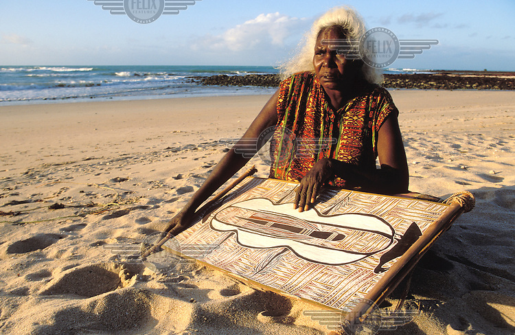 Dhuwarrwarr Marika, an Aboriginal artist from Yirrkala sits on the beach with one of her paintings.