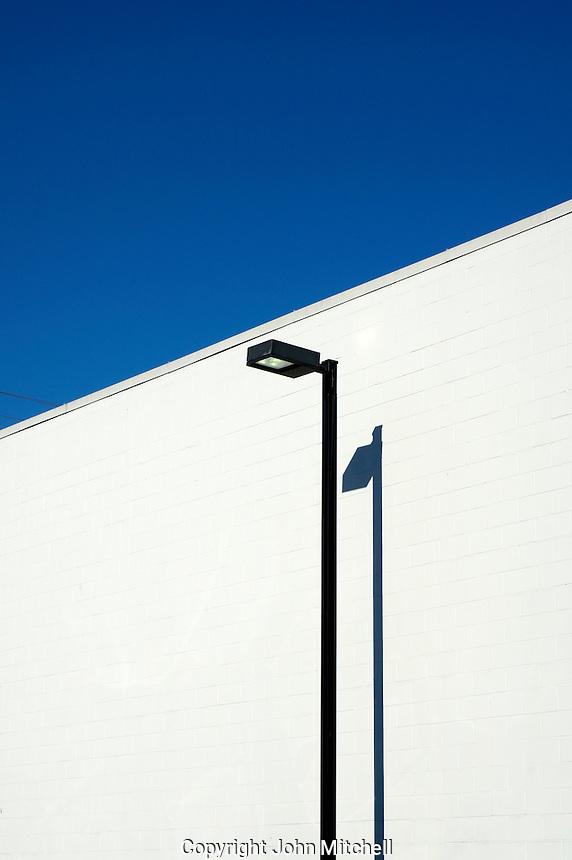 Black lamp post against a stark white wall