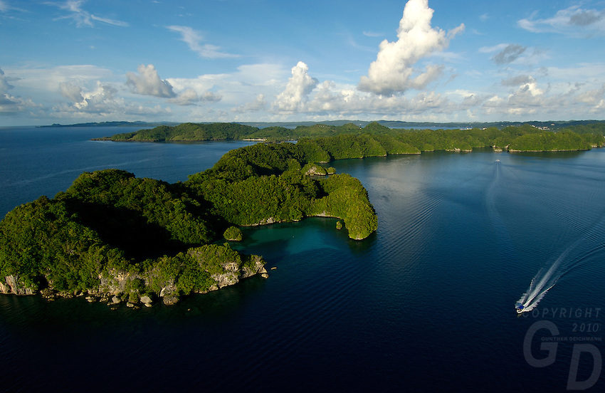 Aerial of the Rock Islands,Palau, Micronesia with Pinchers lagoon in the foreground and a boat cruising by