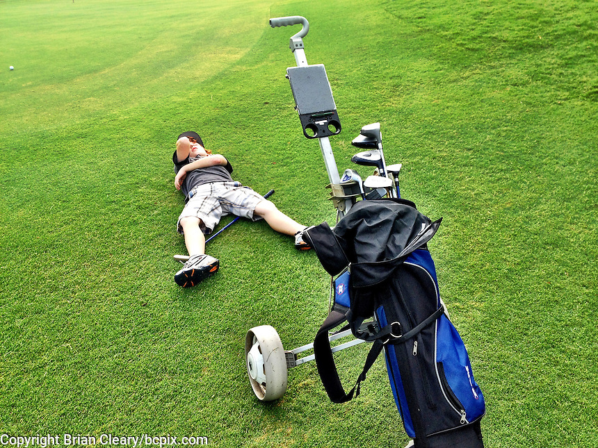 A young golfer fakes exhaustion as he lies on the ground on a Florida golf course, iPhone photo from the archive at www.bcpix.com. (Photo by Brian Cleary/www.bcpix.com)