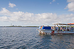 A park service boat brings swimmers and snorklers back to shore, with the turkey Point Power Plant as a back drop.