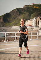 UK Weather: Aberystwyth, Ceredigion, West Wales <br />A woman jogs along the seafront