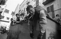 Storico Carnevale di Ivrea, Battaglia delle Arance. Un lanciatore esausto riposa le braccia appoggiandosi al carro --- Historic Carnival of Ivrea, Battle of the Oranges. An exhausted thrower resting his arms on the wagon