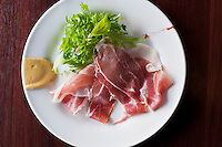 A plate of parma ham or proscuito served with a side salad and mustard.
