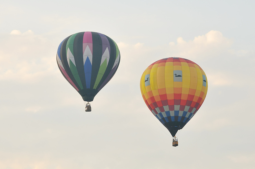 In pairs, the balloons float off into the pale morning sky.