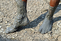 The feet of a villager caked in mud. Since May 2006, more than 10,000 people in the Porong subdistrict of Sidoarjo have been displaced by hot mud flowing from a natural gas well that was being drilled by the oil company Lapindo Brantas. The torrent of mud - up to 125,000 cubic metres per day - continued to flow three years later.